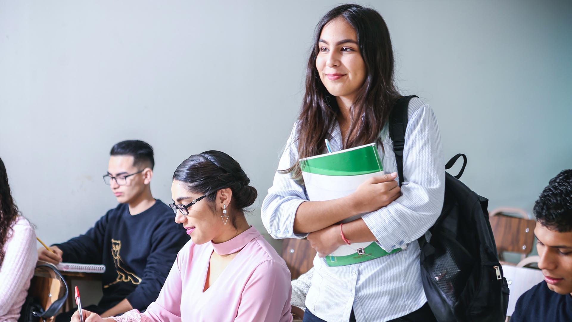 Tjej står i ett klassrum med en grön anteckningsbok