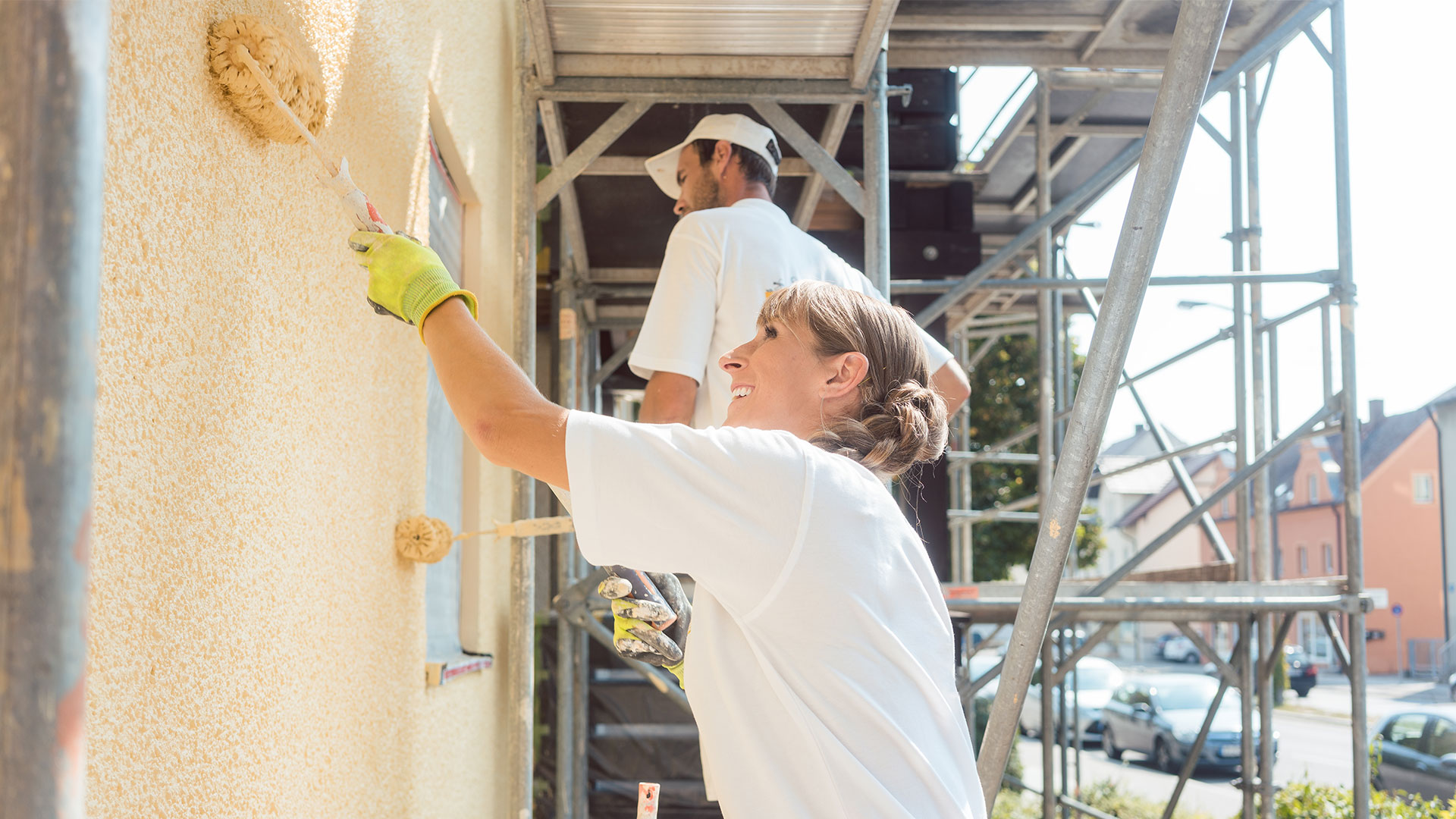 Två målare som målar en fasad